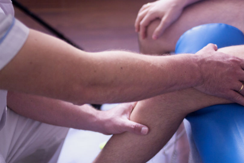 Physical therapist examining patient's knee